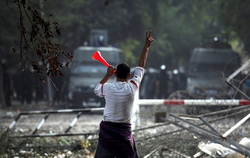 An Egyptian protester blows a stadium horn as he gestures at a cordon of security forces near Tahrir Square, where an opposition rally has been called to voice rejection of President Mohammed Morsi's seizure of near-absolute powers, in Cairo on Tuesday, Nov. 27, 2012. Demonstrators and police clashed just hours ahead of a planned mass rally by opponents of the country's Islamist president, who are demanding he rescind decrees that granted him near-absolute powers. (AP Photo/Khalil Hamra)