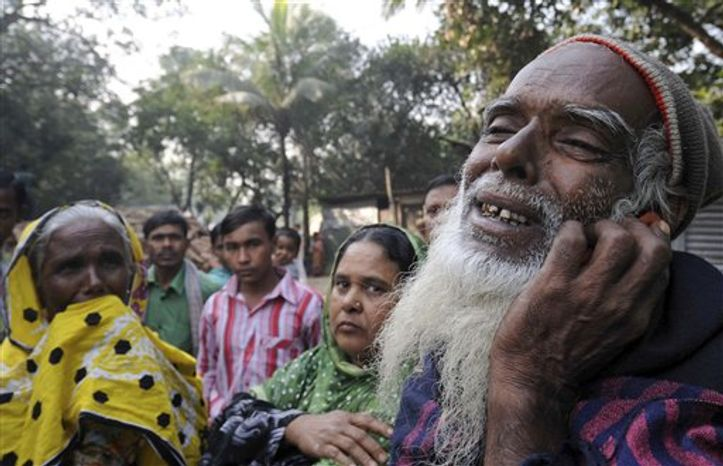 A Bangladeshi man, right, reacts as he looks for his son's body outside a garment factory where a fire killed more than 110 people Saturday on the outskirts of D