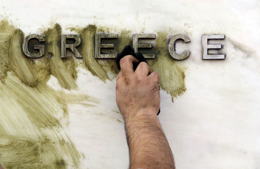 A worker cleans graffiti off the Bank of Greece logo outside the central bank's headquarters in Athens on Monday, Nov. 26, 2012. (AP Photo/Thanassis Stavrakis)