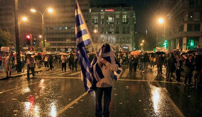 A protester takes cover from the rain after a protest near the parliament during clashes in Athens on Wednesday Nov. 7, 2012. (AP Photo Nikolas Giakoumidis)