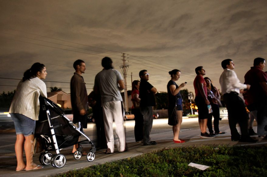 Voters line up in the dark to beat the 7 p.m. deadline to cast their ballots at a polling station in Miami on Tuesday, Nov. 6, 2012. House Republicans, still smarting from their poor showing among Hispanics in the presidential election, are planning a vote in late November 2012 on immigration legislation that would both expand visas for foreign science and technology students and make it easier for those with green cards to bring their immediate families to the United States. (AP Photo/Wilfredo Lee)