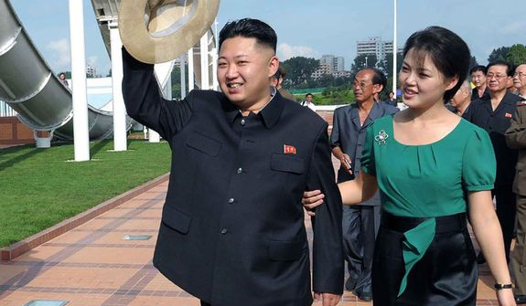 In this Wednesday, July 25, 2012, photo released by the Korean Central News Agency and distributed in Tokyo by the Korea News Service, North Korean leader Kim Jong-un, accompanied by his wife Ri Sol-ju, waves to the crowd as they inspect the Rungna People's Pleasure Ground in Pyongyang, North Korea. (AP Photo/Korean Central News Agency via Korea News Service)