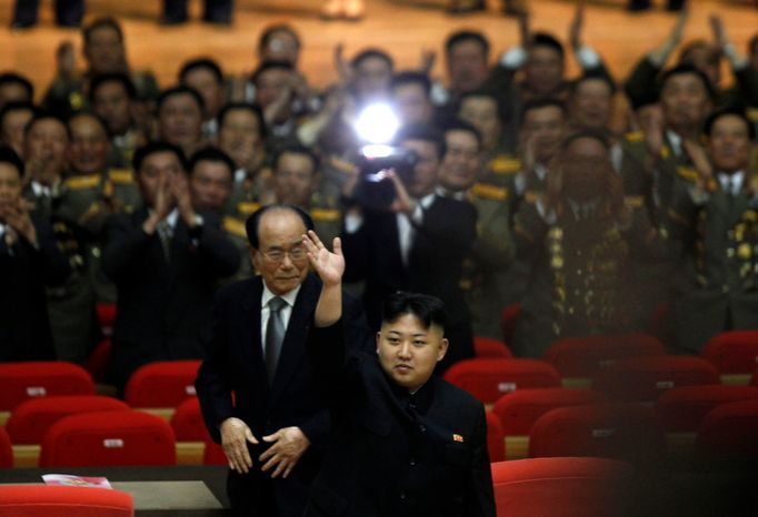"""North Korea's new commander in chief, Kim Jong-un, waves as he walks ahead of Kim Yong-nam, president of the Presidium of the Supreme People's Assembly, after attending a concert to mark the 80th anniversary of the founding of the North Korean army, in Pyongyang, North Korea, on Wednesday, April 25, 2012. North Korea is armed with """"powerful modern weapons"""" capable of defeating the United States, a top military chief in Pyongyang said Wednesday, a claim that matches the country's regular rhetoric but is questioned by experts. (AP Photo/Ng Han Guan)"""