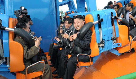 In this undated photo released by the Korean Central News Agency and distributed in Tokyo by the Korea News Service on Thursday, July 26, 2012, North Korean leader Kim Jong-un (center) reacts on a ride as he attends the completion ceremony of the Rungna People's Pleasure Ground in Pyongyang, North Korea. (AP Photo/Korean Central News Agency via Korea News Service)