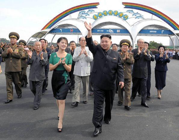 In this Wednesday, July 25, 2012, photo released by the Korean Central News Agency and distributed in Tokyo by the Korea News Service on Thursday, July 26, 2012, North Korean leader Kim Jong-un (foreground right), accompanied by his wife, Ri Sol-ju (foreground left), waves as they attend the completion cerem