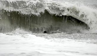 The surf at Big Lagoon beach creates a moderate undertow on Monday, Nov. 26, 2012, near Trinidad, Calif. A family that tried to rescue their dog from the powerful surf at the beach in Northern California were swept out to sea, leaving the parents dead and their 16-year-old son missing, authorities said. (AP Photo/The Times-Standard, Jose Quezada)