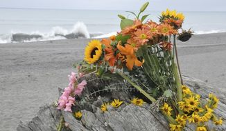 Flowers are rest on a large drift log yards from the breaking surf of the Big Lagoon beach near Trinidad, Calif., on Monday, Nov. 26, 2012. A family that tried to rescue their dog from powerful surf at the beach in Northern California were swept out to sea, leaving the parents dead and their 16-year-old son missing, authorities said. (AP Photo/The Times-Standard, Jose Quezada)