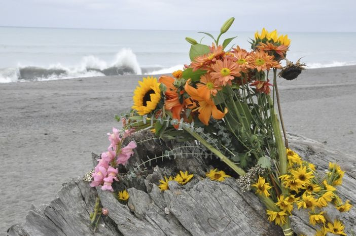 Flowers are rest on a large drift log yards from the breaking surf of the Big Lagoon beach near Trinidad, Calif., on Monday, Nov. 26, 2012. A family that tried to rescue their dog from powerful surf at the beach in Northern California wer