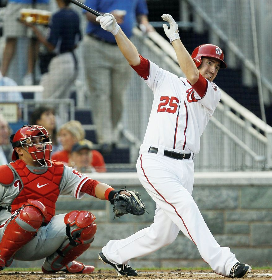 Washington Nationals' Adam LaRoche follows through on a home run as Philadelphia Phillies catcher Carlos Ruiz (51) watches during the second inning of a baseball game, Thursday, Aug. 2, 2012, in Washington. (AP Photo/Carolyn Kaster)