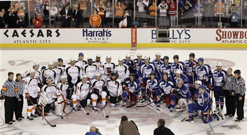 The New Jersey Team, left, and the New York Team pose for photographs after a charity hockey game in Atlantic City, N.J., Saturday, Nov. 24, 2012. New York won 10-6. (AP Photo/Mel Evans)