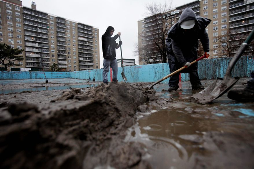 Men shovel out a pool filled with mud on the Rockaway Peninsula in the New York borough of Queens on Tuesday, Nov. 27, 2012. (AP Photo/Seth Wenig)