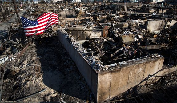** FILE ** An American flag hangs amid the wreckage on Thanksgiving Day in the Breezy Point community of the Rockaways in the New York borough of Queens on Thursday, Nov. 22, 2012. (AP Photo/John Minchillo)