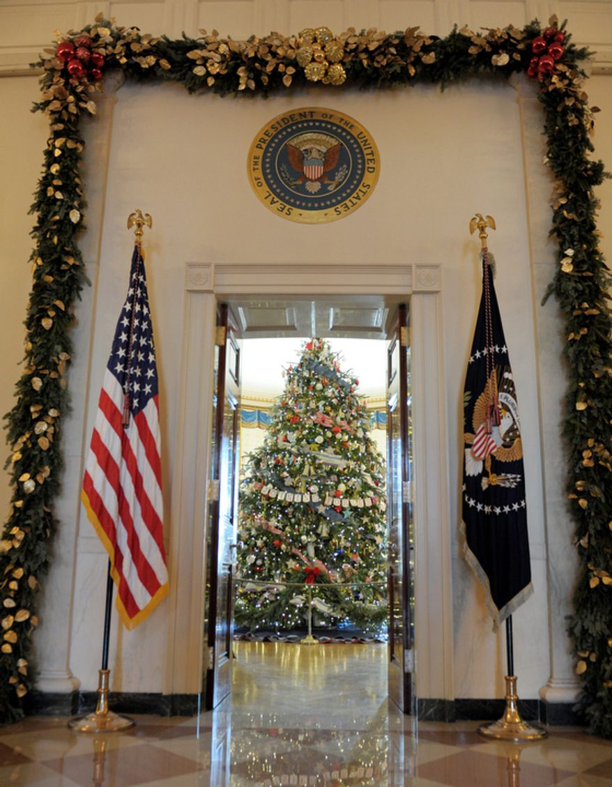 The official White House Christmas tree, an 18-foot-6-inch Frasier fur from Jefferson, N.C., trimmed with ornaments decorated by children of military families, sits in the Blue Room of the White House in Washington, Wednesday, Nov. 28, 2012, during a preview of the White House holiday decorations. (AP Photo/Susan Walsh)