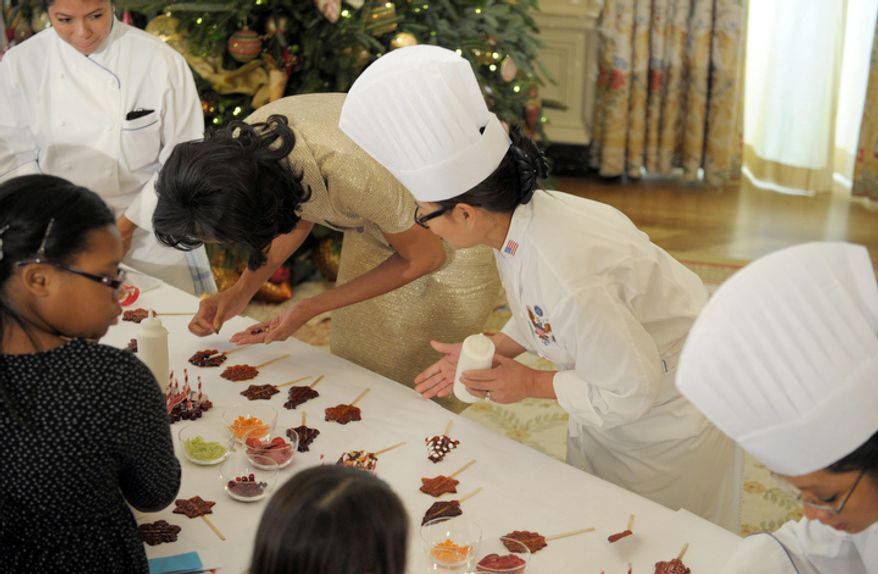 First lady Michelle Obama decorates a lollipop during a holiday decoration preview at the White House in Washington, Wednesday, Nov. 28, 2012. Obama joined children as they decorated holiday treats during a preview of the White House holiday decorations. (AP Photo/Susan Walsh)