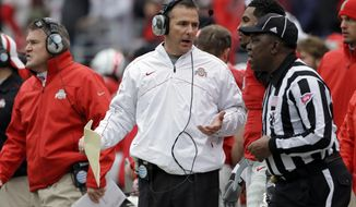 Ohio State head coach Urban Meyer, in white, on the sidelines during an NCAA college football game against Michigan Saturday, Nov. 24, 2012, in Columbus, Ohio. (AP Photo/Mark Duncan)