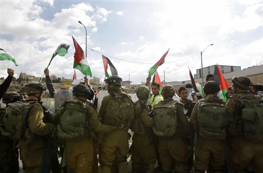 Palestinians, foreign and Israeli activists stand in front of Israeli soldiers as they try to block a road near the West Bank town of Bethlehem, as part of a demonstration in support of the Palestinian statehood petition at the U.N. General Assembly, Wednesday, Nov. 14, 2012. (AP Photo/Nasser Shiyoukhi)