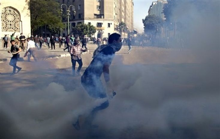 Egyptian protesters clash with security forces near Tahrir square, in Cairo, Egypt, Wednesday, Nov. 28, 2012. Egyptian state television says the country's highest appeal court has decided to suspend its work