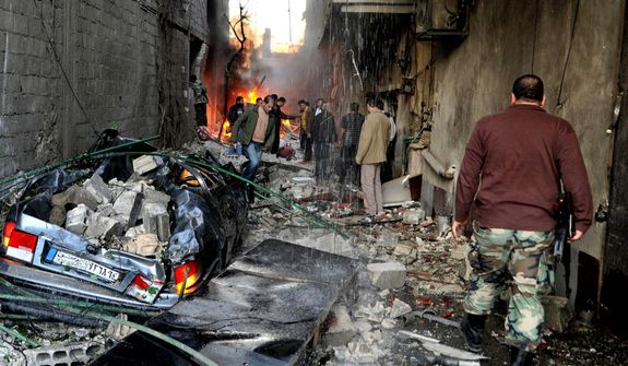 In this photo released by the Syrian official news agency SANA, a Syrian soldier (right) and others gather at an alley that was destroyed by two cars bombs in Jaramana neighborhood of Damascus, Syria, on Wednesday, Nov. 28, 2012. (AP Photo/SANA)