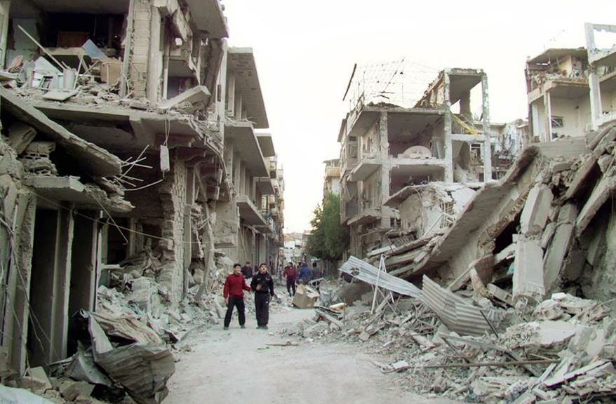 In this citizen journalism image authenticated by AP reporting, Syrian citizens walk in a street in Homs province that was attacked by Syrian warplanes on Wednesday. Internet service was down in the country and cellphone service disrupted. (Associated Press)