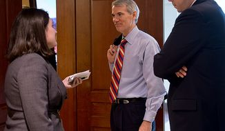 Sen. Rob Portman (center), Ohio Republican, center, talks with a reporter about the closed-door briefing he and other members of the Homeland Security and Governmental Affairs Committee received about the Benghazi attack on Thursday, Nov. 29, 2012, at the U.S. Capitol. (Barbara L. Salisbury/The Washington Times)