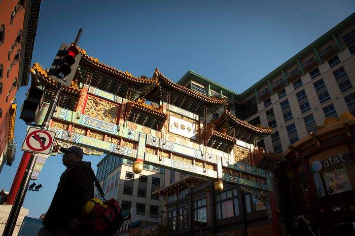 A man is silhouetted against the sunlit Chinatown arch in Chinatown near Seventh and H streets Northwest in Washington on Wednesday, Nov. 28, 2012