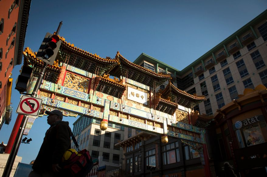 A man is silhouetted against the sunlit Chinatown arch in Chinatown near Seventh and H streets Northwest in Washington on Wednesday, Nov. 28, 2012. (The Washington Times)