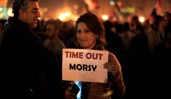 A protester holds a placard against the Egyptian president at an opposition rally in Tahrir Square in Cairo on Tuesday, Nov. 27, 2012. (AP Photo/Khalil Hamra)