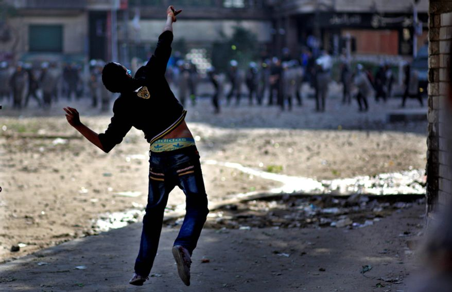 Egyptian protesters clash with security forces near Tahrir Square in Cairo on Wednesday, Nov. 28, 2012. Egyptian state television says the country's highest appeal court has decided to suspend its work nationwide to protest the president's decrees giving himself nearly absolute powers. (AP Photo/Khalil Hamra)