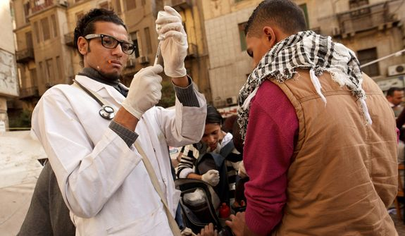 A volunteer doctor at a field hospital in Tahrir Square in Cairo prepares an injection for a protester wounded during clashes with security forces on Thursday, Nov. 29, 2012. (AP Photo/Maya Alleruzzo)