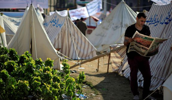An Egyptian protester reads the Wafd, a local newspaper, next to tents occupied by protesters in Tahrir Square in Cairo on Wednesday, Nov. 28, 2012. Egyptian state television says the country's highest appeal court has decided to suspend its work nationwide to protest the president's decrees giving himself nearly absolute powers. (AP Photo/Khalil Hamra)