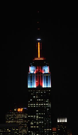 The top floors of New York's Empire State Building are lit in gold, red, blue and white light on Monday, Nov. 26, 2012, after a new LED illumination system was switched on by R&B star Alicia Keys. (AP Photo/Empire State Building, Bryan Smith)