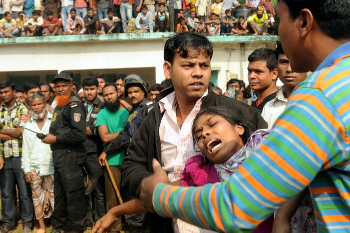 ** FILE ** People console a woman whose relative was killed in a fire at a garment factory outside Dhaka, Bangladesh, Sunday, Nov. 25, 2012. At least 112 people were killed late Saturday night in a fire that raced through the multi-story garme