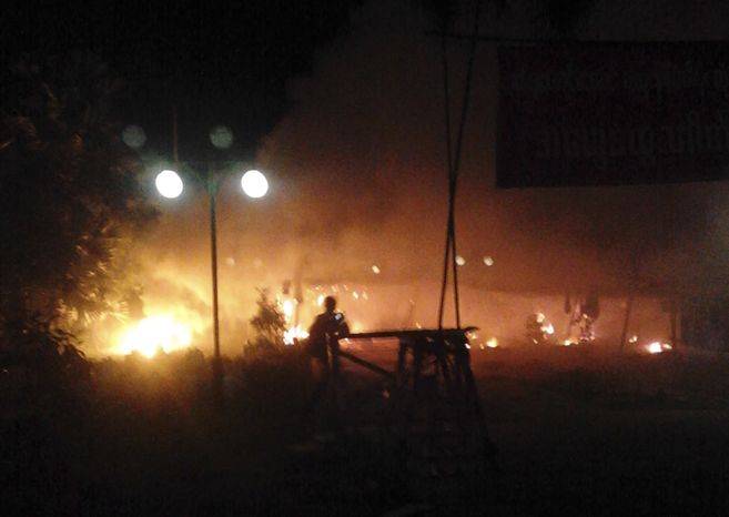 In this early Nov. 29, 2012, photo provided by a monk, flames are seen at the gate of Chinese mining partner Wan Bao where protesters camped before the police crackdown in Monywa, northwestern Myanmar. (AP Photo)