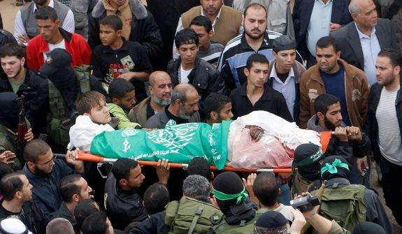 Palestinian Hamas militants carry the covered body of Nidal Hassan during funerals for five Hamas members in Mugharka, Gaza Strip, on Thursday, Nov. 22, 2012. The five were killed in an Israeli airstrike on a building belonging to the Abu Kamil family the previous day, Palestinian health officials said. (AP Photo/Adel Hana)