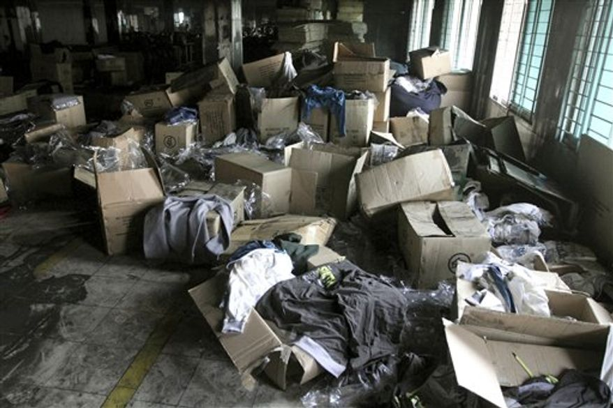 ** FILE ** In this Wednesday, Nov. 28, 2012, file photo, boxes of garments lay near equipment charred in the fire that killed 112 workers Saturday at the Tazreen Fashions Ltd. factory, on the outskirts of Dhaha, Bangladesh. The horrific fire that killed 112 people, Saturday, Nov. 24, 2012, has put the spotlight back on those factory workers and their sometimes treacherous work environment. (AP Photo/Ashraful Alam Tito, File)