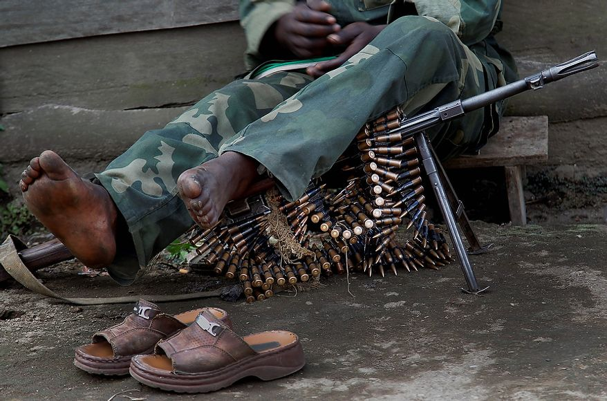 A soldier of the  Mai Mai militia rests in  Kirotshe, some 30 kms south-west of Goma, Thursday Nov. 29, 2012. M23 Rebels, who last week seized one of the most important cities in eastern Congo and advanced beyond, said Thursday that they had pulled back several miles (kilometers ) to the town of Sake and were on track to leave the key city of Goma by Friday, in accordance with a deadline imposed by the international community. Government troops were massing in Minova.(AP Photo/Jerome Delay)