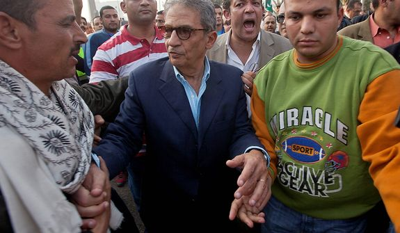 Former foreign minister and presidential candidate Amr Moussa, center, greets supporters as he arrives to Tahrir Square to join other liberal and secular parties for a major protest against Egyptian President Mohammed Morsi's latest decrees granting himself almost complete powers and allowing a rushed constitution to be presented for a vote, Friday, Nov. 30, 2012. (AP Photo/Thomas Hartwell)