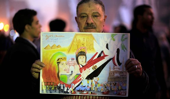 A demonstrator holds a child's portrayal of the Egyptian revolution in Tahrir Square, where liberal and secular parties are holding major protests against Egyptian President Mohammed Morsi's latest decrees granting himself almost complete powers and allowing a rushed constitution to be presented for a vote, Friday, Nov. 30, 2012. (AP Photo/Thomas Hartwell)