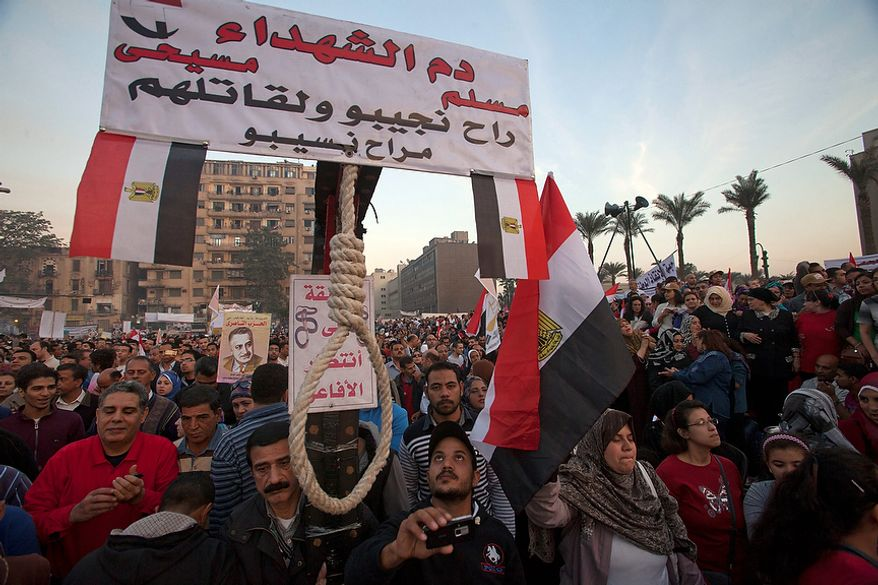 "A demonstrator holds a sign with a noose attached  in Tahrir Square, where liberal and secular parties are holding major protests against Egyptian President Mohammed Morsi's latest decrees granting himself almost complete powers and allowing a rushed constitution to be presented for a vote, Friday, Nov. 30, 2012. Sign in Arabic reads, ""the blood of the martyrs, Muslim Christian, will be revenged and we will never leave their murderers.""  (AP Photo/Thomas Hartwell)"