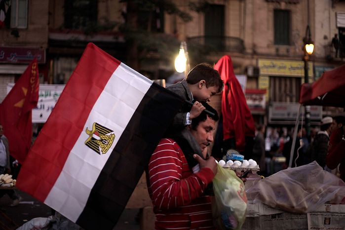 An Egyptian man carries his son during a demonstration in Tahrir Square, Cairo, Egypt, Friday, Nov. 30, 2012. Liberal and secular parties held major protests against Egyptian President Mohammed Morsi's latest decrees granting himself almost complete powers. (AP Photo/Nariman El-Mofty)