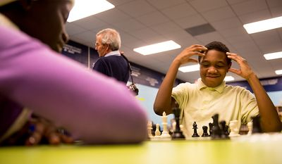 Hart Middle School student Timothy Joyner, 11, right, reacts as he struggles to play Phiona Mutesi, 15, a national chess champion from Uganda, left, as Mutesi visits with District elementary and middle school students in the after school group Chess Challenge in D.C. at Hart Middle School in Southeast, Washington, D.C., Tuesday, November 27, 2012. Chess Challenge in D.C. is a non-profit that teaches the game of chess as well as life skills to students in 24 schools in the District. Mutesi, who is now a international chess player who is also on a book tour, was discovered by Sports Outreach Institute, an evangelical organization that feeds, educates and teaches sports. (Andrew Harnik/The Washington Times)