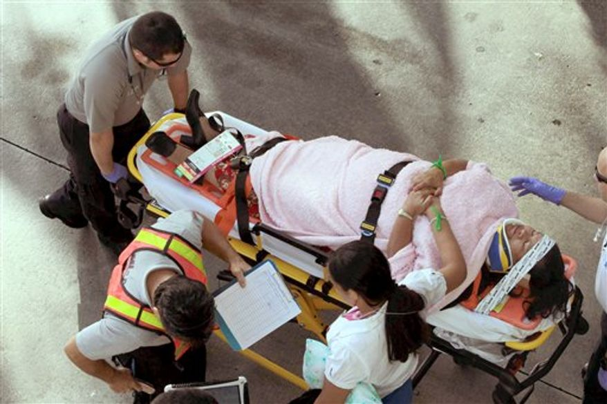 Emergency personnel attend to injured passengers after a bus accident at Miami International Airport on Saturday, Dec. 1, 2012, in Miami. (AP Photo/El Nuevo Herald, Roberto Koltun)