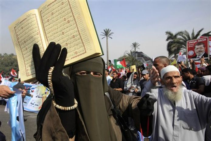 A supporter of Egyptian President Mohammed Morsi holds a Koran and a poster of the president at a rally in front of Cairo University in Cairo, Egypt, Saturday, Dec. 1, 2012. (AP Photo/Thomas