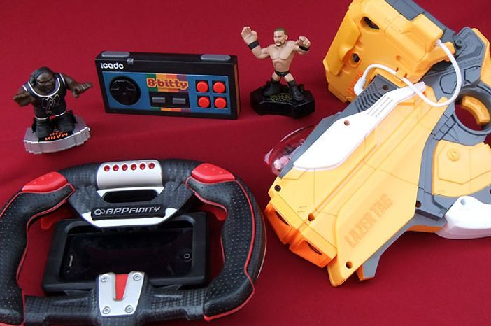 From Left; Mattel's Apptivity WWE Rumblers, Think Geek's iCade 8-Bitty, Spin Master's AppFinity AppDrive and Hasbro's Lazer Tag Blaster are a few gaming gadget gifts for owners of an iPad or iPhone.  (Photo by Joseph Szadkowski/The Washington Times)