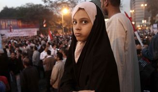 ** FILE ** An Egyptian girl watches supporters of Egyptian President Mohammed Morsi during a rally in front of Cairo University, Giza, Cairo, Egypt, Saturday, Dec. 1, 2012. (AP Photo/Thomas Hartwell)