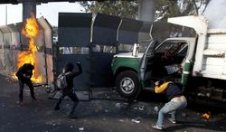 Protestors throw stones over the steel security barriers around the National Congress, where the swearing in of new Mexican President Enrique Pena Nieto is taking place in Mexico City, Saturday, Dec. 1, 2012. (AP Photo/Eduardo Verdugo)