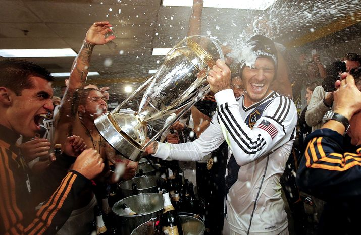 Los Angeles Galaxy's David Beckham, center, of England, is sprayed with champagne as they celebrate in the dressing room after defeating the Houston Dynamo 3-1 in the MLS Cup championship soccer game, Saturday, Dec. 1, 2012, in Carson, Calif. (AP Ph
