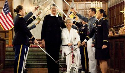 In this photo provided by Outserve-SLDN, Brenda Sue Fulton, center left, and Penelope Gnesin, proceed through an honor guard forming an arch of raised swords after exchanging wedding vows at the U.S. Military Academy at West Point, N.Y. Saturday, Dec. 1, 2012. (AP Photo/Outserve-SLDN, Jeff Sheng)