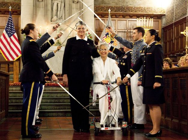 In this photo provided by Outserve-SLDN, Brenda Sue Fulton, center left, and Penelope Gnesin, proceed through an honor guard forming an arch of raised swords after exchanging wedding vows at the U.S. Military Academy at West Point, N.Y. Saturday, Dec