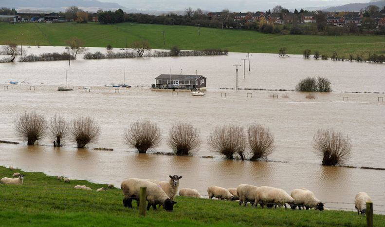 A property stands surrounded by floodwater near the River Severn in Tewkesbury, England, last week as heavy rain continued to fall across Britain, growing the concerns of homeowners and businesses about the cost and availability of flood insurance. (Associated Press)